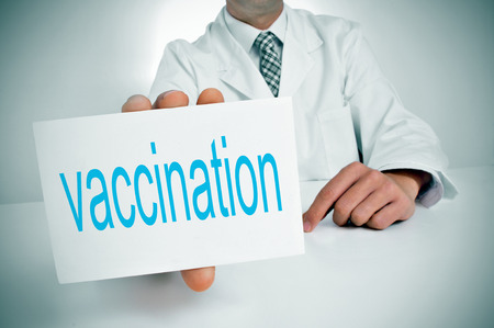 eradication: a man wearing a white coat showing sitting in a desk a signboard with the word vaccination written in it