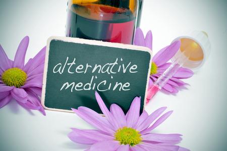 elixir: un frasco cuentagotas y algunas flores con una etiqueta de la pizarra con la medicina alternativa texto escrito en él