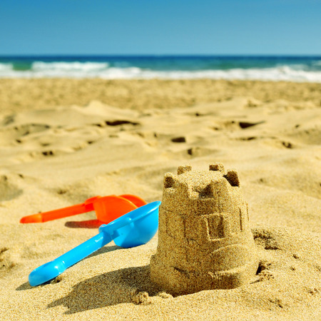 a sandcastle and toy shovels on the sand of a beach, with a retro effect photo