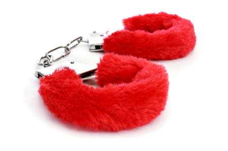 a pair of red sexy fluffy handcuffs on a white background photo