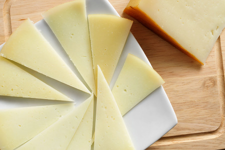 cured: closeup of a piece and some slices of manchego cheese from Spain