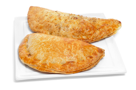 a plate with some different empanadas argentinas, typical argentine stuffed pastries, on a white background Stock Photo