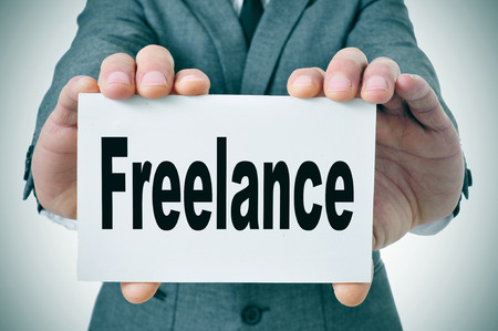 freelance: businessman showing a signboard with the word freelance written in it Stock Photo
