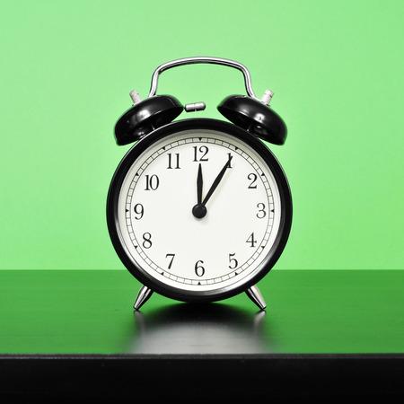 'bedside table': a mechanical alarm clock on a bedside table