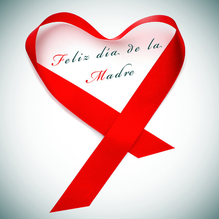 dia de la madre: a red satin ribbon forming a heart and the sentence feliz dia de la madre, happy mothers day written in spanish