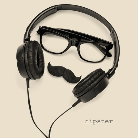 snob: a pair of glasses, a mustache and a pair of headphones, and the word hipster on a beige background Stock Photo