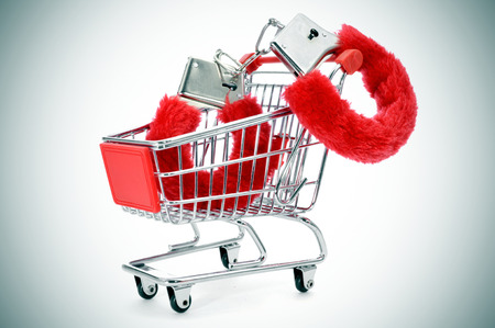 love sex: a pair of red sexy fluffy handcuffs in a shopping cart Stock Photo