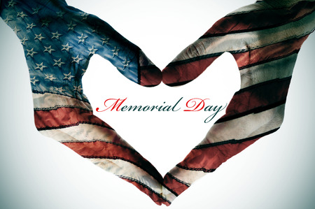 memorial day written in the blank space of a heart sign made with the hands patterned with the colors and the stars of the United States flag Stock Photo