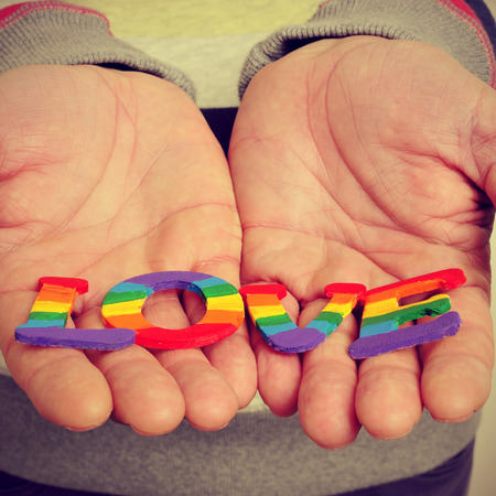 gay men: a young man holding in his hands letters painted as the gay pride flag forming the word love, with a retro effect Stock Photo