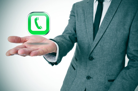 mobile voip: a businessman with a telephone icon in his hand depicting the voice-over-IP apps Stock Photo