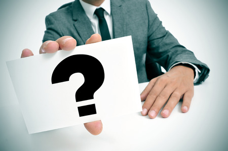 interrogatory: a man wearing a suit sitting in a desk holding a signboard with a question mark Stock Photo