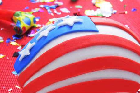 a cupcake decorated as the United States flag on a table with a red tablecloth with a party horn and confetti photo