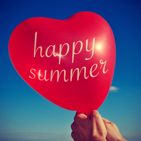 someone holding a heart-shaped balloon with the sentence happy summer written in it, with a retro effect photo