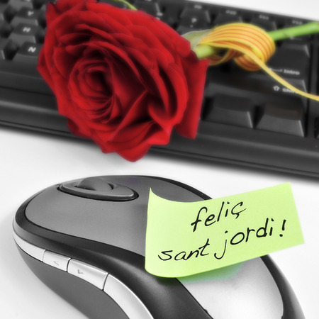 sant: a red rose on a computer keyboard and the sentence felic Sant Jordi, happy Saint Georges Day, written in catalan in an sticky note Stock Photo