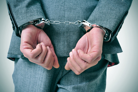 a man wearing a suit with his wrists handcuffed in the back photo