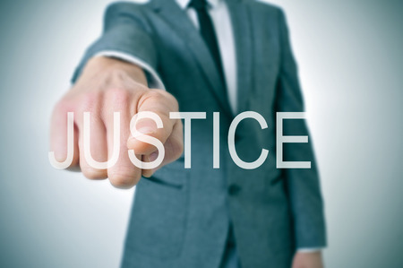 incriminate: man wearing a suit pointing the finger to the word justice written in the foreground