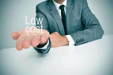 biznesmen siedzi na biurku przedstawiający tekst niski koszt w ręku