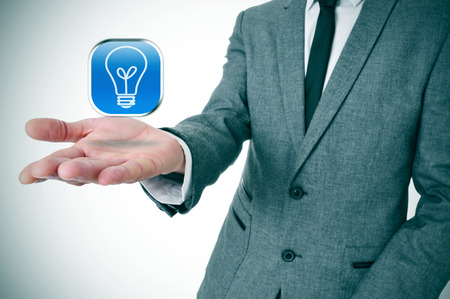 man wearing a suit with an icon with a light bulb in his hand photo