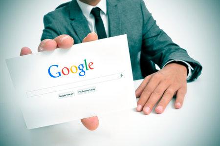 google: BARCELONA, ESPA�A - 26 de septiembre de 2013: El hombre de negocios que sostiene un letrero con la b�squeda web de Google como p�gina de inicio