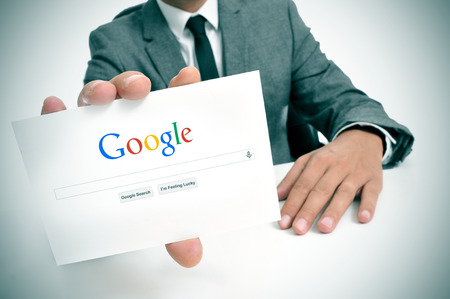 classement: BARCELONE, ESPAGNE - 26 septembre 2013: Homme d'affaires tenant un panneau avec le moteur de recherche Google page d'accueil