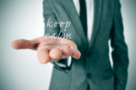 destress: man wearing a suit with the text keep calm in his hand Stock Photo