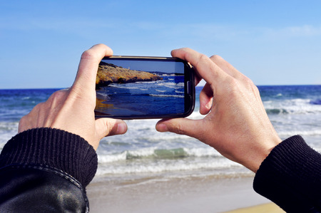 someone taking a picture of a beach with a smartphone photo
