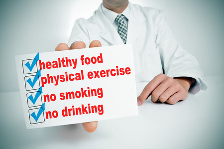 a man wearing a white coat sitting in a desk showing a signboard with some healthy habits, such as healthy food, physical exercise or no smoking photo