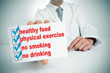 habitos saludables: un hombre que llevaba un abrigo blanco, sentados en un escritorio que muestra un cartel con algunos hábitos saludables, como la alimentación sana, el ejercicio físico o no fumar Foto de archivo