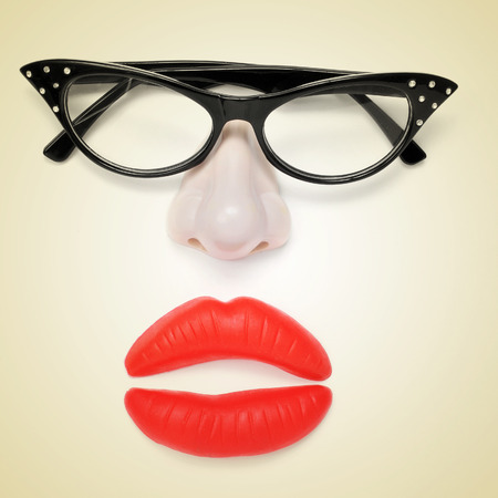 beige lips: a pair of glasses, a fake nose and fake lips forming a woman face on a beige background, with a retro effect Stock Photo
