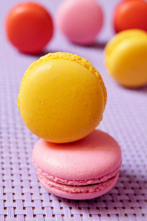 some appetizing macarons with different colors and flavors on a purple background photo