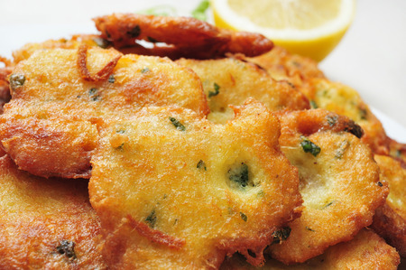 bacalao: closeup of a plate with a pile of tortas de bacalao, spanish cod cakes, on a set table