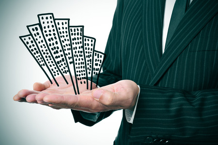 a businessman showing a pile of drawn buildings in his hands