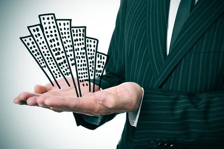 un hombre de negocios que muestra un montón de edificios dibujados en sus manos Foto de archivo