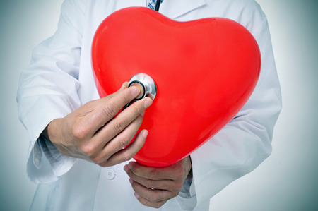 a doctor auscultating a red heart with a stethoscope photo