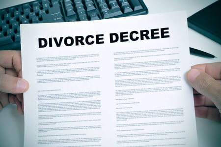 law breaking: closeup of man hands holding a divorce decree on a desk