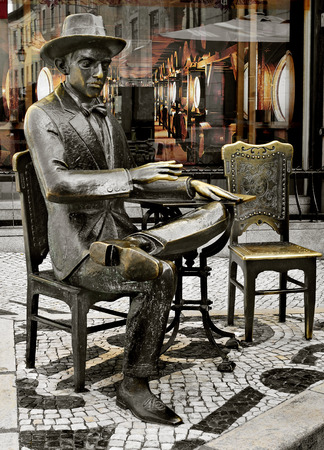 chiado: LISBON, PORTUGAL - MARCH 18: Statue of Fernando Pessoa outside of Cafe A Brasileira on March 18, 2014 in Lisbon, Portugal. This iconic statue and the cafe itself are visited for thousands of tourists Editorial