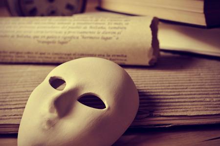 극작과 공연 예술의 개념을 묘사 한 책과 마스크의 더미,