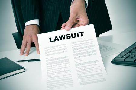 derecho penal: un abogado en su oficina que muestra un documento con la demanda texto escrito en ella