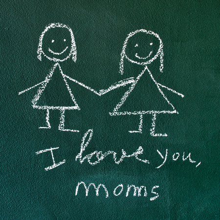the sentence I love you, moms handwritten with chalk in a chalkboard, with a drawing of a lesbian couple photo