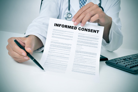consent: a doctor in his office showing an informed consent document and pointing with a pen where the patient must to sign Stock Photo