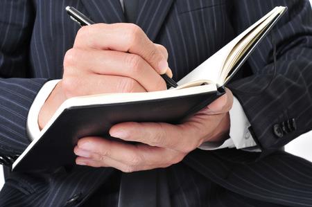 advising: closeup of a businessman writing in a notebook