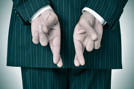 crossing fingers: a man wearing a suit crossing his fingers in his back Stock Photo