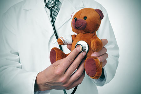 a doctor auscultating a teddy bear with bandages in its head and arm, depicting the pediatric medicine or the veterinary medicine concepts photo