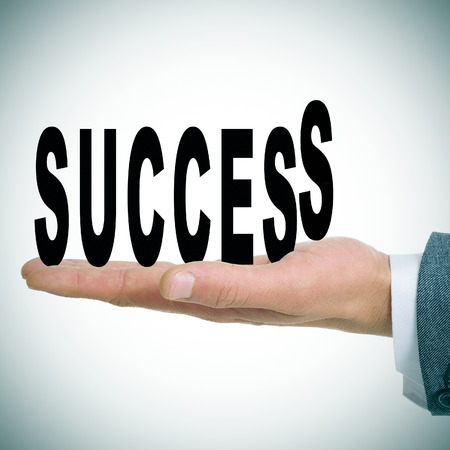 businessman with the word success in the palm of his hand photo