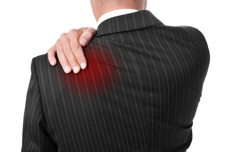 man wearing a suit with his hand in his back because of his backache photo