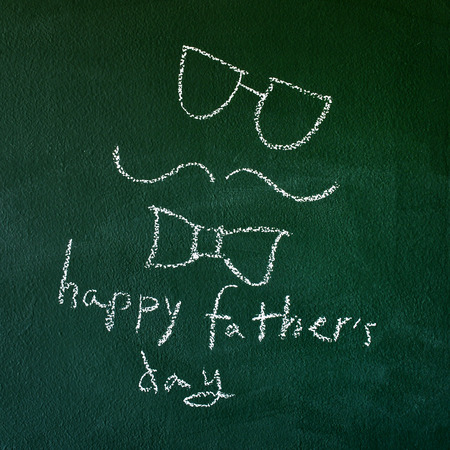 the sentence happy fathers day handwritten with chalk in a chalkboard, with a drawing of a man face photo