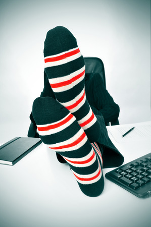 chilling out: a businessman relaxing in the office with his feet on the desk
