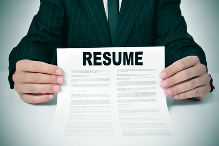 job qualifications: a man wearing a suit showing his resume Stock Photo