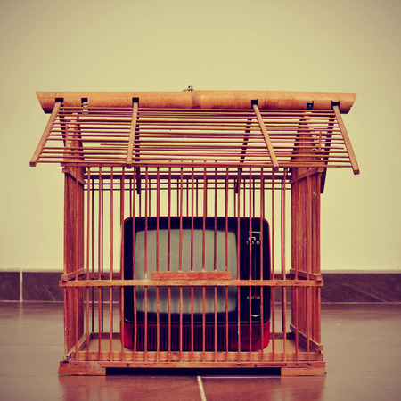 an ancient red television in a birdcage with a retro effect photo