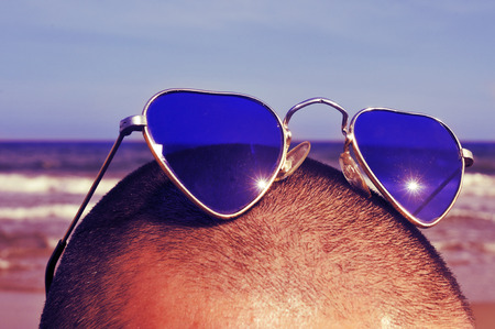 closeup of the head of a man with heart-shaped sunglasses on the beach, with a retro effect photo